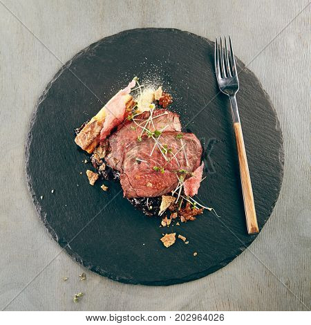 Medallions of veal with gratin from potatoes and onion and meat sauce with fresh herbs on dark stone plate. Gastronomic restaurant menu. Top View