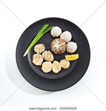 Teppanyaki Japanese and Korean Grill Food - Sea scallop with mushrooms with lemon slice and fresh herbs on  black plate on white isolated background. Raw food preparation for frying on teppan