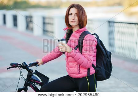 Adult Beautiful Redhead Woman With Bob Haircut Thinking Drinking Morning Coffee Posing On Bicycle In