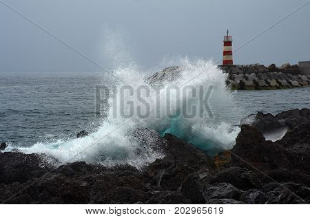 Atlantic ocean surf and lighthouse on the breakwater