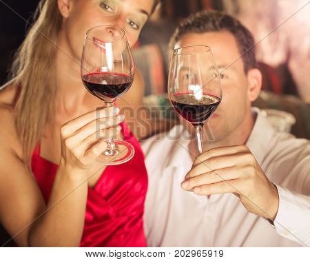 Couple tasting red wine in cellar at winetasting with glasses in their hands