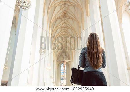 Woman looking at interior of big cathedral
