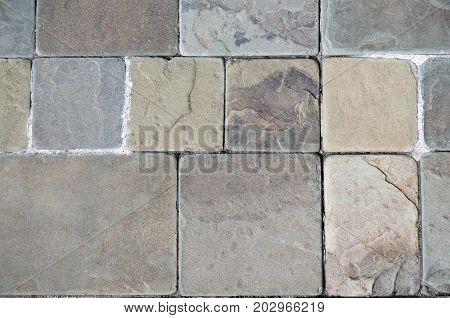 Stone floor in warm colors. Background of stone bricks of different sizes. Top view