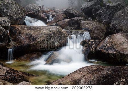 Foggy day near waterfall of Studeny potok stream in the National Park High Tatra Slovakia