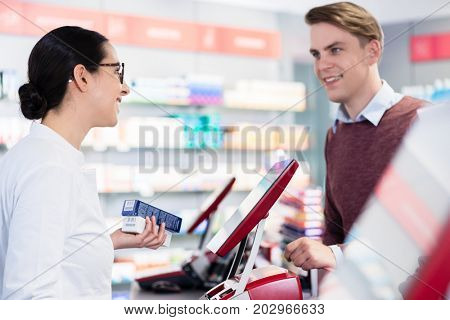 Side-view of a cheerful pharmacist holding two packs of prescribed medicine while giving advices, and useful information to a young male customer in a modern drugstore