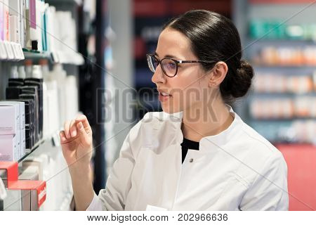 Side view close-up portrait of a dedicated female pharmacist standing in front of the pharmacy shelves, with various products while thinking to make the best choice