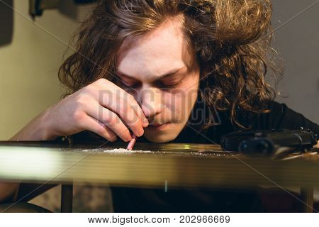 Close-up of the face of a drug addicted teenage boy holding a rolled bill while snorting cocaine from a glass table at home