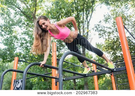 Low-angle view of a fit woman smiling while exercising single-arm plank outdoors on the equipment of a modern calisthenics park in summer