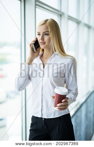 Busy Businesswoman Use The Phone With Cup Of Coffee In Other Hand Near Big Panoramic Window In The O