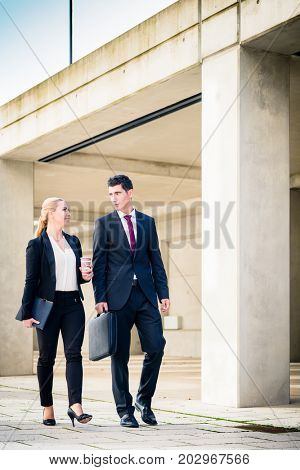 Business people walking to the next meeting in front of concrete architecture in city