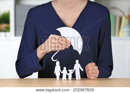 Woman holding umbrella over paper silhouette of family on table. Insurance concept