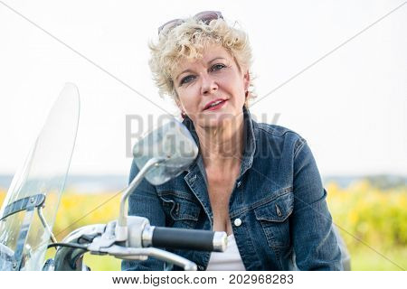 Portrait of an active senior woman wearing a blue denim jacket while sitting on a motorcycle in the countryside in springtime
