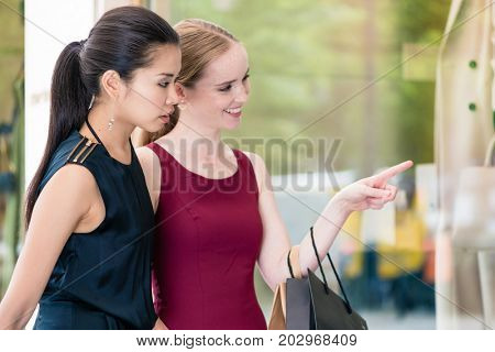 Two female best friends looking at the latest fashion trends with different attitudes while shopping together downtown
