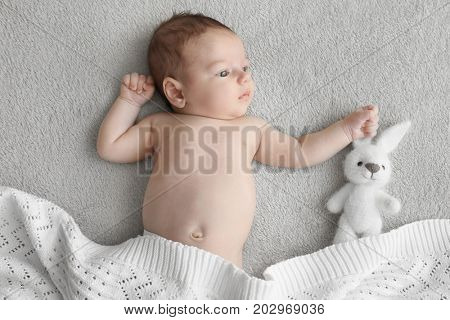 Cute little baby with toy lying on soft plaid at home