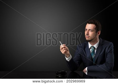 Businessman holding cigarette in his hand and wearing suit.