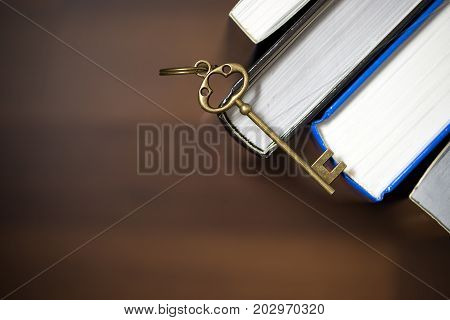 Key on hardback books over brown background with copy space