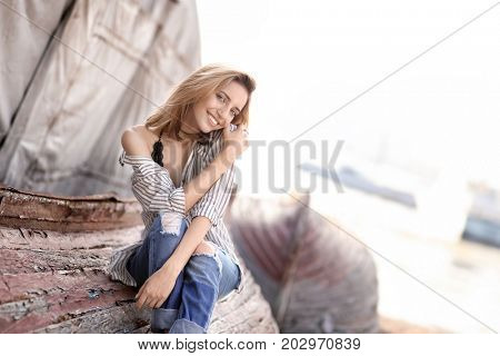 Young woman sitting on old overturned boat outdoors