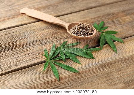 Spoon with hemp seeds on wooden background