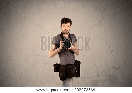 A professional male photographer with belt holding a camera and taking photos in front of clear grey urban wall background concept