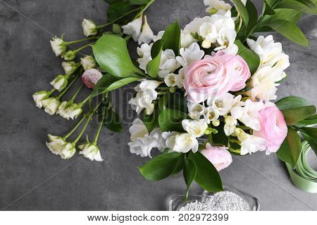 Composition with beautiful freesia flowers on gray background