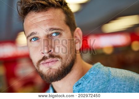 Outdoor p ortrait of young caucasian man standing in underground walkway wearing casual clothes.