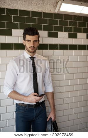 Handsome young man holding mobilephone, standing at underground station.