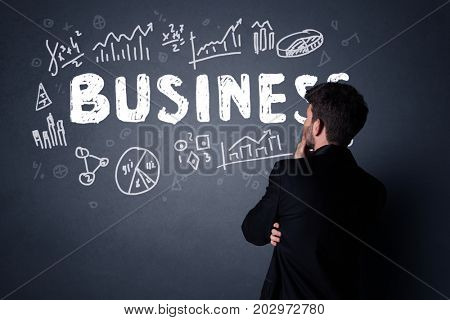 Young businessman in black suit standing in front of a detailed business plan
