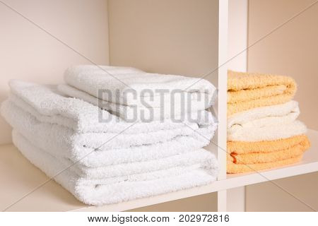 Stacks of clean fresh towels on shelves