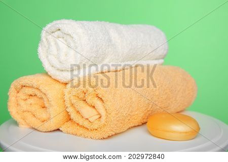 Rolled towels and soap on table against color background