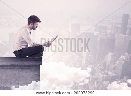 An elegant young businessman sitting on the edge looking over urban city landscape with clouds concept