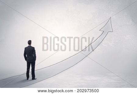 Adult elegant male with briefcase standing on drawn grey arrow pointing up financial concept
