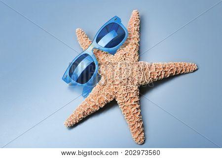 Beautiful sunglasses with starfish on light background