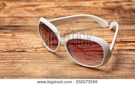 Beautiful sunglasses on wooden background