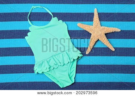 Little girl's swimsuit with starfish on color background
