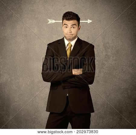 A confused young business guy giving thumbs up with a drawn arrow going through his head concept