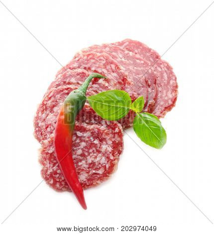 Delicious sliced sausage with chili pepper and basil on white background
