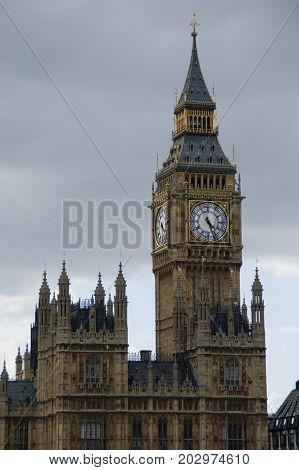 Big Ben behind and over the Houses of Parliament in Westminster, London on a cloudy day