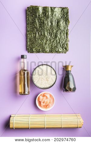 The sushi ingredients on purple table. Rice, ginger, soy sauce, vinegar and nori sheets.