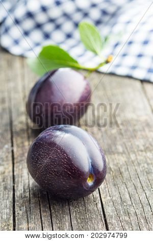 Two fresh plums on old wooden table. Blue plums with leaves.