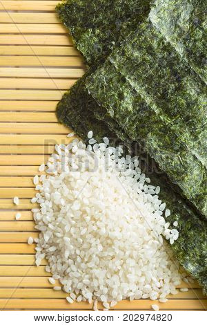 Green nori sheet and sushi rice on bamboo mat. Top view.