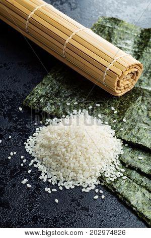 Green nori sheet , rice and bamboo mat on black table.