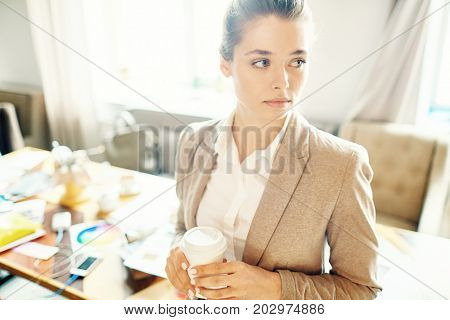 Attractive young white collar worker looking away pensively while standing at open plan office with paper cup of coffee in hands, waist-up portrait