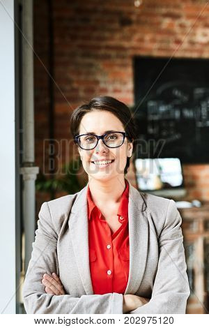 Waist-up portrait of confident middle-aged entrepreneur looking at camera with toothy smile while standing at window of modern office