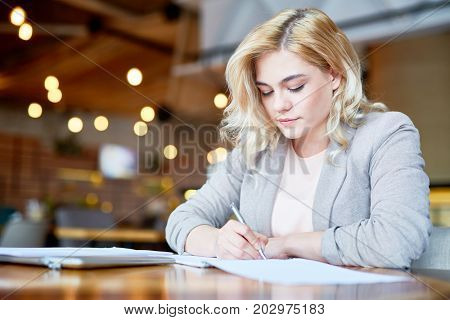 Concentrated young entrepreneur in formalwear taking necessary notes while preparing for important negotiations, interior of modern cafe on background