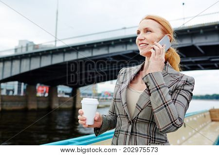 Cheerful business leader calling her subordinate during travel
