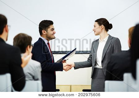 Coach congratulating one of business course attendants on graduation event