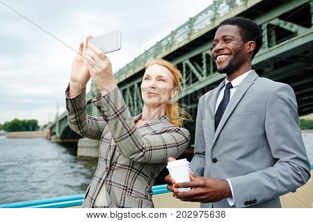Happy associates making selfie during travel by steamship