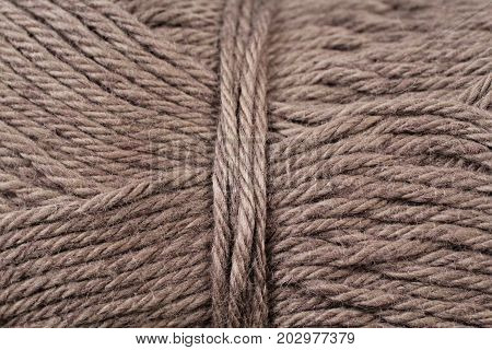 A super close up image of drab brown yarn