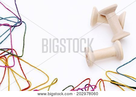 colorful threads and wooden spool on white background