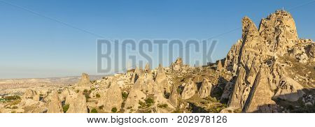 Ancient town and a castle of Uchisar dug from a mountains after sunrise, Cappadocia, Turkey.Panorama